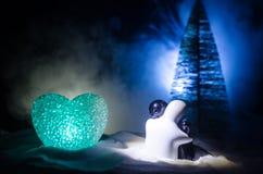 Konzept des Liebes-neuen Jahres Keramische Zahlen des Mädchens und des Jungen umarmt sich und steht auf dem weißen Schnee und far Stockfoto