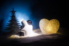 Konzept des Liebes-neuen Jahres Keramische Zahlen des Mädchens und des Jungen umarmt sich und steht auf dem weißen Schnee und far Stockbild