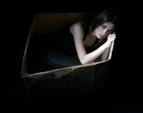 Konzept des Obdachlosen Umgekipptes Mädchen in der Pappschachtel Stockbilder