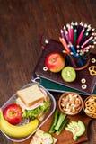 Konzept des Schulmahlzeitbruches mit gesunder Brotdose und Schulbedarf auf hölzernem Schreibtisch, selektiver Fokus Stockbild