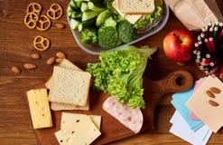 Konzept des Schulmahlzeitbruches mit gesunder Brotdose und Schulbedarf auf hölzernem Schreibtisch, selektiver Fokus Lizenzfreie Stockfotografie