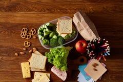Konzept des Schulmahlzeitbruches mit gesunder Brotdose und Schulbedarf auf hölzernem Schreibtisch, selektiver Fokus Stockbilder