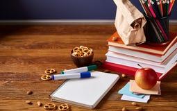 Konzept des Schulmahlzeitbruches mit gesunder Brotdose und Schulbedarf auf hölzernem Schreibtisch, selektiver Fokus Stockfotografie