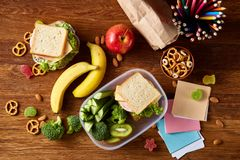 Konzept des Schulmahlzeitbruches mit gesunder Brotdose und Schulbedarf auf hölzernem Schreibtisch, selektiver Fokus Stockfotos