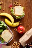 Konzept des Schulmahlzeitbruches mit gesunder Brotdose und Schulbedarf auf hölzernem Schreibtisch, selektiver Fokus Stockfoto