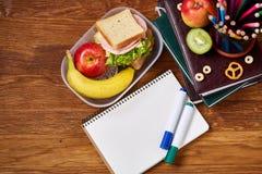 Konzept des Schulmahlzeitbruches mit gesunder Brotdose und Schulbedarf auf hölzernem Schreibtisch, selektiver Fokus Lizenzfreie Stockbilder