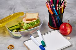 Konzept des Schulmahlzeitbruches mit gesunder Brotdose und Schulbedarf auf weißem Schreibtisch, selektiver Fokus Lizenzfreie Stockfotos