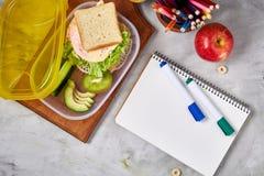 Konzept des Schulmahlzeitbruches mit gesunder Brotdose und Schulbedarf auf weißem Schreibtisch, selektiver Fokus, flache Lage Stockfotografie