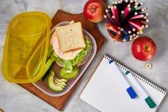 Konzept des Schulmahlzeitbruches mit gesunder Brotdose und Schulbedarf auf weißem Schreibtisch, selektiver Fokus, flache Lage Lizenzfreie Stockfotografie