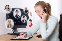 Konzept des Sozialen Netzes - Geschäftsfrau, die am Telefon in O spricht Stockbild