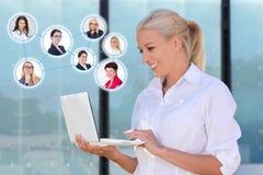 Konzept des Sozialen Netzes - Geschäftsfrau mit Laptop im stree Lizenzfreie Stockfotos