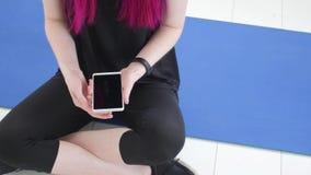 Konzept des Sports und der Eignung Junge Sportlerin, die Eignung Verfolger und Smartphone sitzt und verwendet stock video footage