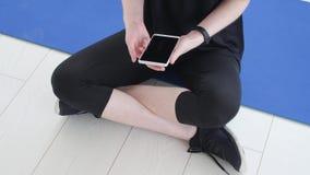 Konzept des Sports und der Eignung Junge Sportlerin, die Eignung Verfolger und Smartphone sitzt und verwendet stock footage