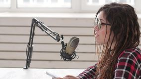 Konzept des Str?mens und des Rundfunks Junges nettes M?dchen im Studio spricht in ein Mikrofon stock video footage