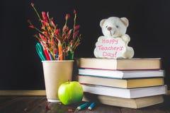 Konzept des Tages des Lehrers Gegenstände auf einem Tafelhintergrund Bücher, grüner Apfel, Bär mit einem Zeichen: Der Tag des glü Stockbild