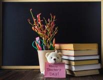 Konzept des Tages des Lehrers Gegenstände auf einem Tafelhintergrund Bücher, grüner Apfel, Bär mit einem Zeichen: Der Tag des glü Stockfoto