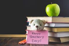 Konzept des Tages des Lehrers Gegenstände auf einem Tafelhintergrund Bücher, grüner Apfel, Bär mit einem Zeichen: Der Tag des glü Lizenzfreies Stockfoto
