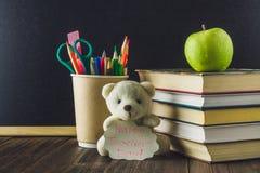 Konzept des Tages des Lehrers Gegenstände auf einem Tafelhintergrund Bücher, grüner Apfel, Bär mit einem Zeichen: Der Tag des glü Lizenzfreie Stockfotografie