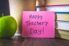 Konzept des Tages des Lehrers Gegenstände auf einem Tafelhintergrund Bücher, grüner Apfel, Plakette: Der Tag, die Bleistifte und  Stockfotos