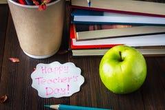 Konzept des Tages des Lehrers Gegenstände auf einem Tafelhintergrund Bücher, grüner Apfel, Plakette: Der Tag, die Bleistifte und  Lizenzfreies Stockbild