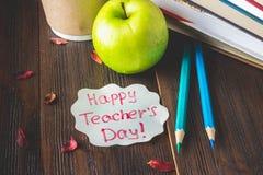 Konzept des Tages des Lehrers Gegenstände auf einem Tafelhintergrund Bücher, grüner Apfel, Plakette: Der Tag, die Bleistifte und  Stockfoto