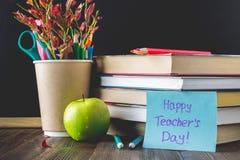 Konzept des Tages des Lehrers Gegenstände auf einem Tafelhintergrund Bücher, grüner Apfel, Plakette: Der Tag, die Bleistifte und  Lizenzfreie Stockfotografie