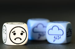 Konzept des traurigen Sturmwetters - Emoticon und Wetter würfeln auf blac Stockfotografie