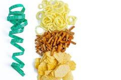 Konzept des Treffens von Wahl der Nahrung Ungesunde Nahrung: Chips, cpackersonion Ringe gegen messendes Band, flache Lage stockbilder