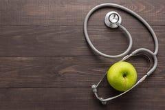 Konzept für Gesundheitswesen, Stethoskop und grünen Apfel auf hölzernem Ba Lizenzfreie Stockfotografie