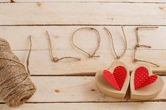 Konzept für Liebesgeschichten und für Valentinstag Die Schnur, die Aufschriften von ihr und handgemachte Pappherzen auf einem nat stockbilder