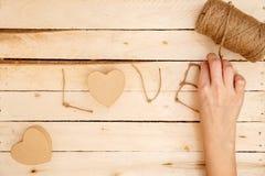 Konzept für Liebesgeschichten und für Valentinstag Weibliche Hände stellen Kästen in Form von einem Herzen und der Aufschrift 'Li lizenzfreie stockfotografie