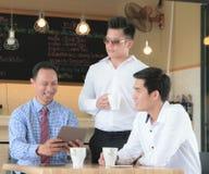 Konzept-Geschäftsgespräch, das Relex in der Kaffeestube, Tabellentablette trifft stockfoto