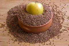 Konzept - Gewichtsverlust Buchweizen in einem keramischen Teller und in einem Apfel Stockfotos