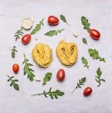 Konzept kochend, nisten Sie Teigwaren Kirschtomaten Arugula und Draufsicht des rustikalen hölzernen Hintergrundes des Knoblauchs Stockfotografie