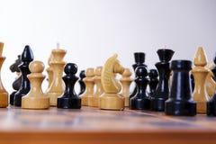 Konzept mit Schachfiguren auf einem hölzernen Schachbrett Lizenzfreie Stockbilder