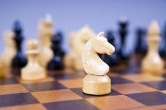 Konzept mit Schachfiguren auf einem hölzernen Schachbrett Stockbild