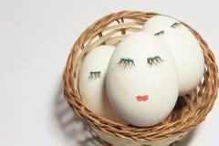 Konzept Ostern drei Eier mit Augen und den Lippen in einem Weidenkorb Lizenzfreies Stockfoto