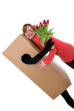 Konzept: Paketbefreier mit Blumen umarmt eine Frau Lizenzfreie Stockbilder