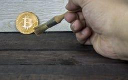 Konzept von cryptocurrency Technologie Archäologe, der weg von bitcoin Münze mit einem Bürsteninstrument abwischt Lizenzfreies Stockbild