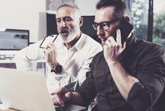 Konzept von den Geschäftsleuten, die Prozess treffen Bärtiger junger Mann, der den Handy- und Erwachsenkollegen schaut zum Laptop Stockbild