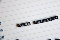Konzept von Gene Theraphy-Wort auf hölzernen Würfeln mit Büchern im Hintergrund lizenzfreie stockfotos