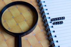 Konzept von Reduce Risiko auf hölzernen Würfeln mit Büchern im Hintergrund lizenzfreie stockfotos