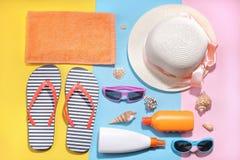 Konzept von Sommerferien Verschieden sahnt, Gläser, Hut und Tuch mit an einem farbigen Hintergrund Beschneidungspfad eingeschloss stockfotografie