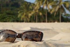 Konzept von Strandferien und -reise Brown-Sonnenbrille im Sand auf dem Strand, Ozean Lizenzfreie Stockbilder