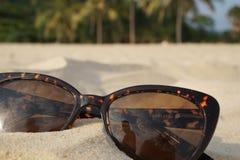 Konzept von Strandferien und -reise Brown-Sonnenbrille im Sand auf dem Strand, Ozean Stockfotos