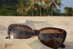 Konzept von Strandferien und -reise Brown-Sonnenbrille im Sand auf dem Strand, Ozean Lizenzfreie Stockfotografie