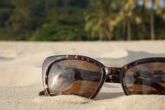 Konzept von Strandferien und -reise Brown-Sonnenbrille im Sand auf dem Strand, Ozean Stockbilder