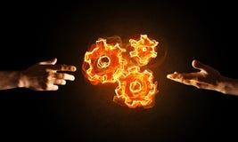 Konzept von Teamworking oder von Organisation stellte sich durch Hände in glühenden Zahnrädern der Note und des Feuers dar Stockfoto