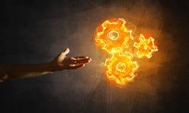 Konzept von Teamworking oder von Organisation stellte sich durch Hände in glühenden Zahnrädern der Note und des Feuers dar Stockfotos