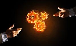 Konzept von Teamworking oder von Organisation stellte sich durch Hände in glühenden Zahnrädern der Note und des Feuers dar Lizenzfreies Stockfoto